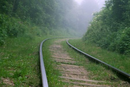 Steep turn of railways in the green forest with a misty obscure view ahead