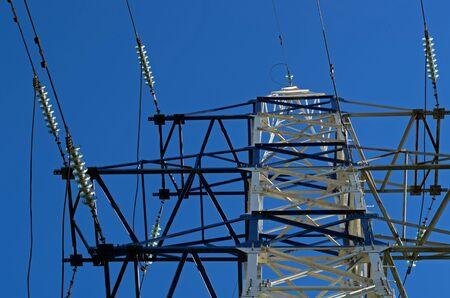 La construcción de metal blanco es la torre de transmisión de electricidad con cables contra un cielo azul