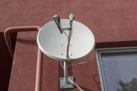 Round white metal satellite TV antenna attached by anchor bolts to brown facade of an apartment building to the left of the window and to the right of the arch. A gas pipeline pipe is visible nearby. Banco de Imagens