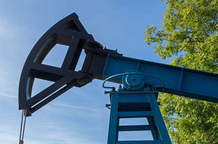 Industrial block pumping unit with blue painted framed body and black rocking element with flexible rope against cloudy blue sky and green tree foliage Stockfoto