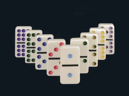 Close-up of dominos with colorful dots isolated on a black background.