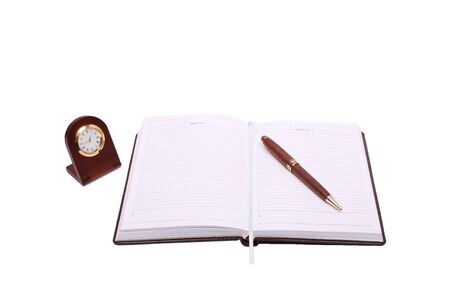 brown notebook pen and clock isolated over white photo