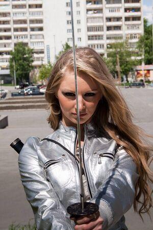grassy plot: hembra joven con espada de samurai al aire libre  Foto de archivo