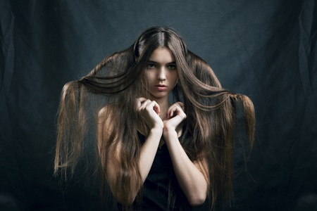 portrait of a beautiful woman with perfect hair on a dark background photo