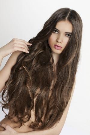 capelli lunghi: bella donna con la pelle perfetta e lunghi capelli ricci su sfondo bianco