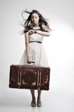 watch movement: portrait of a beautiful girl with long and developing hair with a suitcase in his hand on a white background Stock Photo