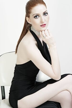 Fashion portrait of a beautiful woman in sexy black dress photo