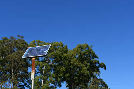 Vintage solar panel with trees and blue sky background