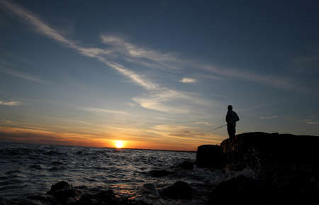 hitch hiker: WEIPA QUEENSLAND, AUSTRALIA - MAY 31: A fisherman casts his fishing rod at sunset off the rocks outside of Weipa in Far North Queensland. 31 May 2011 AUSTRALIA