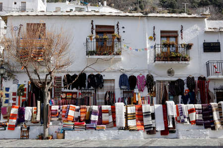 hand woven: PAMPANEIRA, SPAIN - DECEMBER 1: A shopfront displays hand woven blankets in the town of Pampaneira,Las Alpujarras, Spain. 12 December 2015