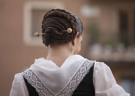 Valencia, Spain- October 9th, 2010: Fallera woman, with typical clothes and traditional braided bun  Editorial