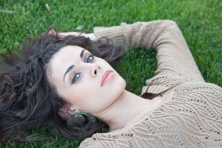 green eyed attractive woman lying on the grass   photo