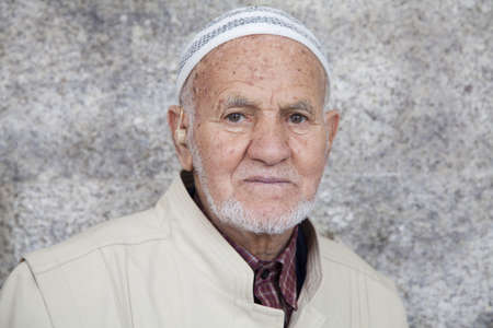 Caceres, Spain - April 22, 2011: portrait of a man with wrinkled face of Arab origin with typical cap called taqiya, staring into the camera, posing on gray wall background