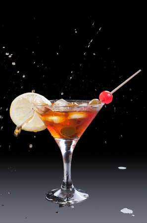 glass of vermouth with ice and splashes down photo