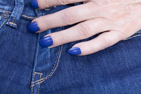 jeans and a female hand with blue nail polish photo