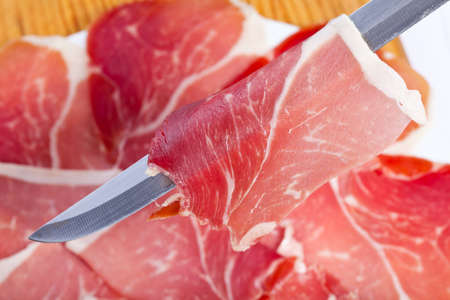 cut slices of ham with a carving knife on the plate out of focus Stock Photo