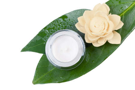 jar of face cream on wet leaves and a flower beige