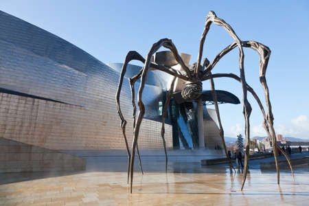 Bilbao, Spain, December 24. Bronze sculpture, steel and marble shaped spider by Louise Bourgeois, called mama and is located at the rear comtemporáneo Art Museum Bilbao Guggenheim, the Canadian architect Frank O. Gehry, opened in 1997. You can see peopl