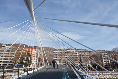 Bilbao, Spain-January 1. Hanging White Bridge on the River Nervi�n, designed by architect Santiago Calatrava, which opened in 2007. The floor is covered with a carpet, as the original glass was highly slippery in wet weather city. There are people crossi