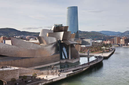 Bilbao, Spain, January 1, 2012. Guggenheim Museum of Contemporary Art, Canadian architect Frank O. Lehry, seen from the river Nervión with Iberdrola Tower in the background, of Cesar Pelli. You can see the artificial lake, next to the terrace and the spi