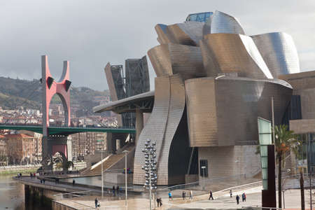 Bilbao, Spain, December 24, 2011. Guggenheim Museum of Contemporary Art, designed by architect Frank O. Gehry, on the banks of the river Nervi�n with La Salve Bridge in the background. There are people walking