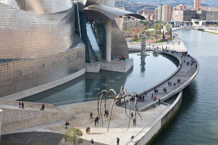 Bilbao, Spain, January 1, 2012. Artificial lake in the back of the Guggenheim Museum of Contemporary Art, designed by architect Frank O. Lehry, Nervión riverside, and the sculpture Mom, as Louise Bourgeois spider. There are people walking