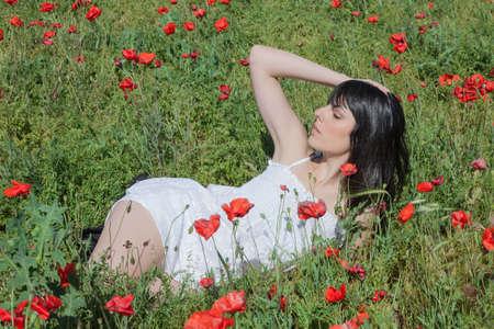 mujer: Chica Joven Que Miente En El Campo En Un campo de maíz, Entre amapolas Stock Photo