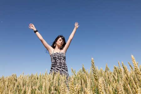 feliz: Niña En Un campo de maíz Levanto los Brazos Stock Photo