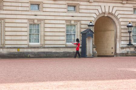 royal guard: London, UK - May 16, 2016; Facade of Buckingham Palace with a Royal Guard doing his round