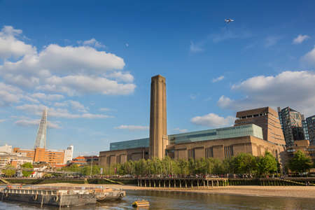 London, UK - May 16, 2016; View of the Tate Modern Gallery, with the skyscraper The Shard in the background, from the River Thames. There are people walking and a plane in the sky Editorial
