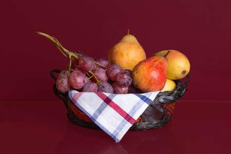 Autumn fruit basket on garnet background