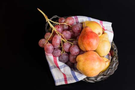 Autumn fruit basket on black background