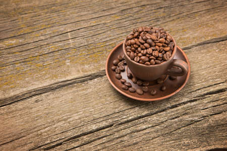mocca: Coffee beans in a cup on old boards, rustic style