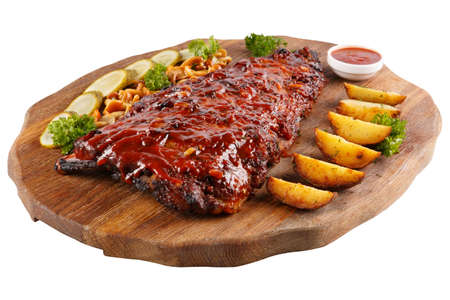 Meat grilled ribs on a white background, on a board with baked potatoes, cucumbers and pickled mushrooms