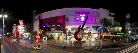 Cancun, Mexico - December 15, 2011: Night panoramic of the entertainment district at Forum in Cancun Mexico. This area is near the convention center and has night clubs, restaurants and shopping which includes: Coco Bongo Show and Disco, Hard Rock Cafe,