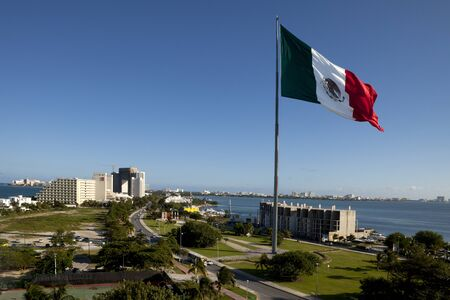Large flag of Mexico flying high near resort area of Cancun