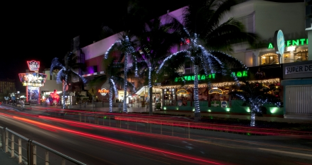 Cancun, Mexico - December 15, 2011: Night panoramic of the entertainment district at Forum in Cancun Mexico. This area is near the convention center and has night clubs, restaurants and shopping which includes: Coco Bongo Show & Disco, Hard Rock Cafe,