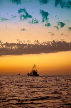 Sport fishing boats heading out just befor sunrise for a day of fishing. Stock Photo - 11995596