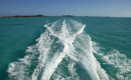 Boat wake leaving a tropical island fast. Stock Photo - 12028489