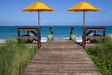 turks: Cubierta que conduce a una playa tropical y el oc�ano azul con dos paraguas amarillo Foto de archivo
