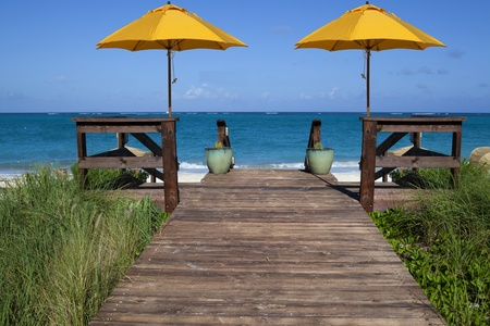 Deck that leads to a tropical blue beach and ocean with two yellow umbrellas