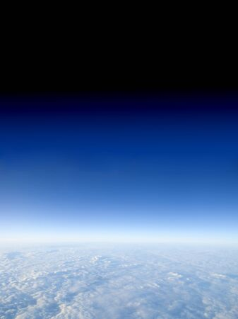 troposphere: A view at 40,000 feet above the clouds with the sky fading to space. this area is known as the troposphere, which begins at the surface and extends to between 9 km (30,000 ft) at the poles and 17 km (56,000 ft) at the equator
