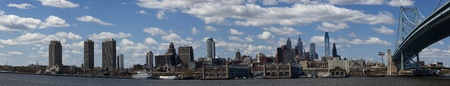Panoramic view of the downtown Philadelphia skyline along the Delaware River , taken from Canden New Jersey  The Ben Franklin Bridge is on the right side of the picture  5 pictures were used to make this panoramic picture photo