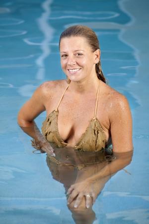 Pretty blond woman in a tan bikini standing in a swimming pool