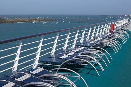 cruiseship: Sillas vac�as en un crucero con vistas a una isla tropical