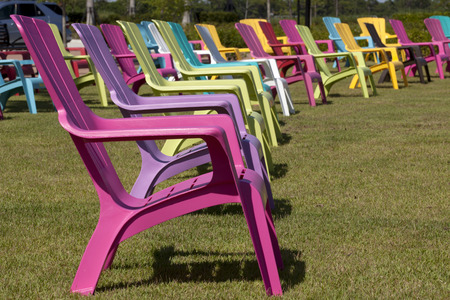 Colorful plastic Adirondack chairs in a park