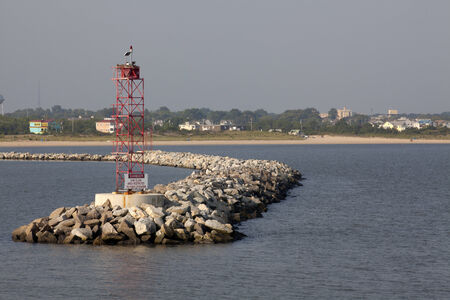 Rock beakwater outside of a harbor at Cape Henelopen with Lewes, Delaware in the background Stock Photo