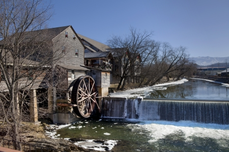 grist mill: Watermill on the Little Pigeon river, in the mountain community of Pigeon Forge, Tennessee during the winter  Ice can be seen along the banks of the river Stock Photo