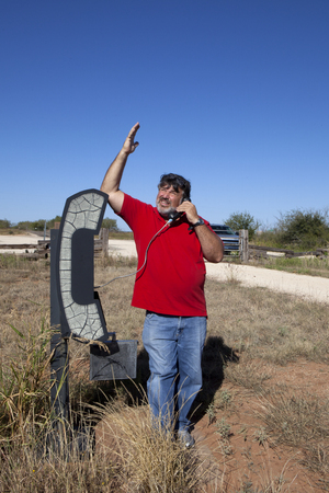 Man using an old phone booth in the middle of no-where photo