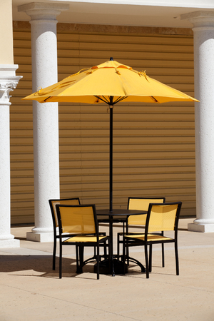 Outdoor table with yellow umbrella and chairs
